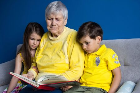 An old grandmother and her beloved grandchildren sit at home and read an interesting book 写真素材