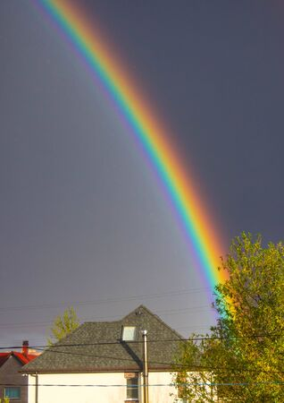 beautiful rainbow after the rain in the background of a stormy sky and houses