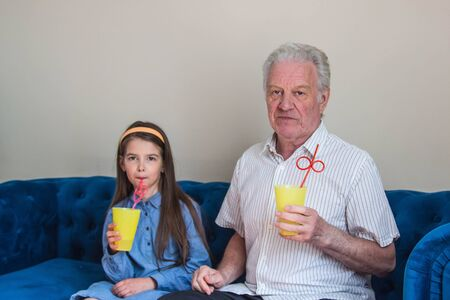 grandfather and granddaughter sit on a blue sofa with glasses of delicious cocktails Stock fotó