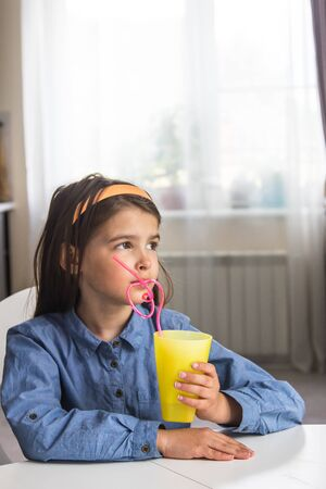 The girl is sitting in the kitchen and drinking a drink from a yellow glass with a straw