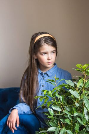 A girl in a denim dress sits and looks out the window in a room with a blue sofa and a flower