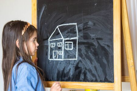 the girl drew a house and the sun with chalk on the Board, so she learns to draw 写真素材