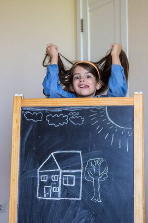 the girl drew a house and sun with chalk on the Board and is happy about it