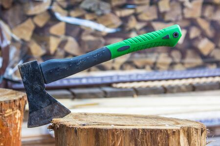 A metal axe stands stuck in a wooden stump after chopping wood