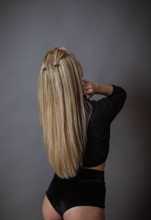 A slender girl in black underwear and long blond hair stands with her back turned