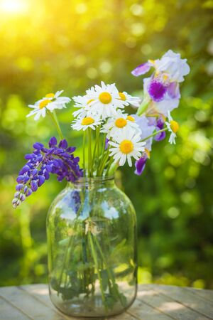Beautiful bouquet of wild flowers in the light of the setting sun in a glass vase