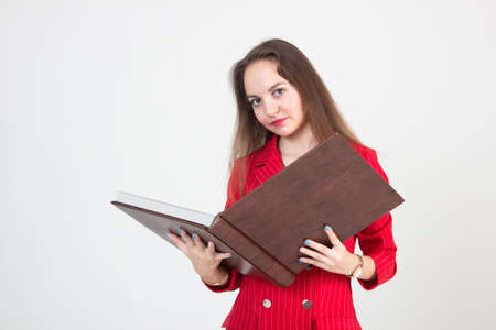 Portrait of a young business woman in a red suit holding a large book with documents on a light background