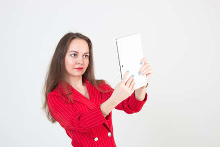 Portrait of a young business woman with beautiful eyes in a red suit taking a selfie