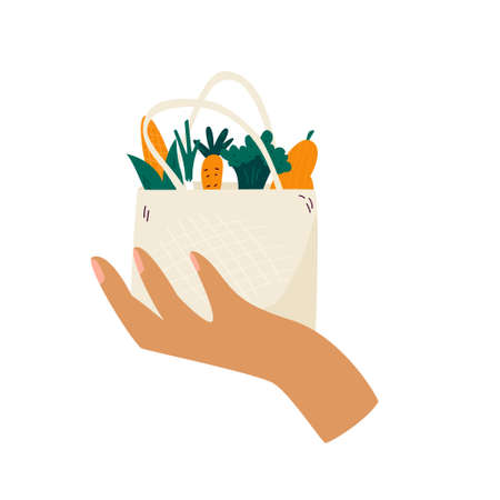 Female hand holding reusable eco bag with organic vegetables. Zero waste concept