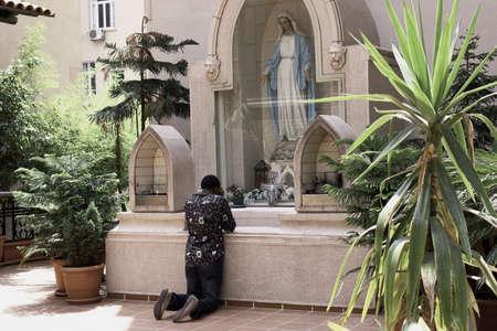 reverent: Black man praying to Virgin Mary