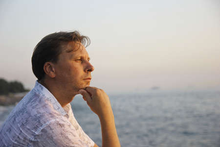Middle-aged man sitting close to the sea and thinking Banco de Imagens