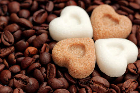 Brown and white sugar hearts lying on roasted coffee beans