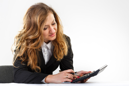 woman thinks on the calculator .In a hand holding a pen