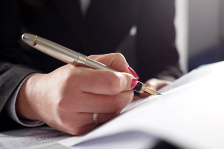 signing authority: Business woman writing fountain pen head.
