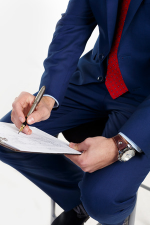 signing authority: Businessman with a clock on the hand writes the document. Stock Photo