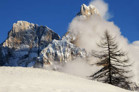 Dolomites Alps, South Tyrol, Italy. Cimon della Pala or Cimone with clouds in the Pale di San Martino Group.