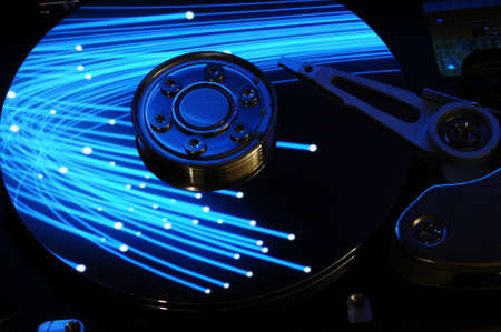 Close up of Computer Hard Drive Disc with abstract colors reflected on the disk surface. Background wallpaper. Stock Photo