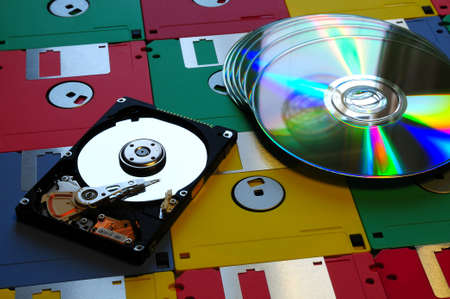 Evolution of digital storage systems. Colored Floppy Disk with a modern DVD and Hard Disk Drive opened. background. Stock Photo
