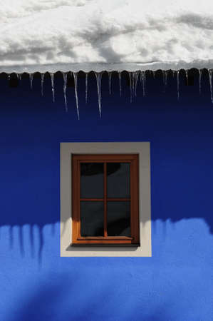 icicles hanging from the roof of a house. Corvara (Alta Badia) in the Dolomites. Italy