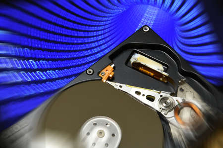 Close Up of Open Hard Disk Drive over future binary code background.