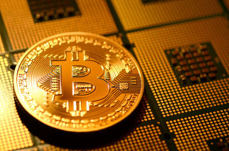 close up of phisical crypt currency bitcoin over computer cpu. background and business concept image.