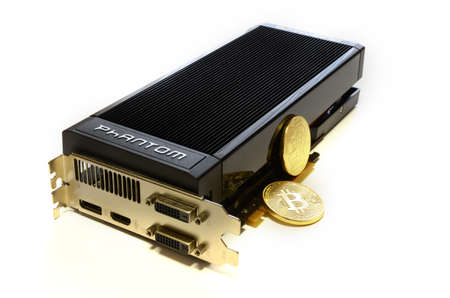 Florence, Italy - March 16, 2018: Cryptocurrency Phisical Gold Bitcoin and modern GAINWARD Nvidia GeForce GTX 670 Phantom Gaming graphics card. Mining equipment.