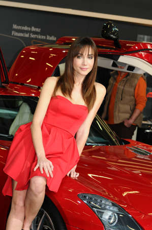 BOLOGNA, ITALY - DECEMBER 2, 2010: beautiful fashion model poses at Mercedes Stand with Mercedes SLS AMG at the Bologna Motor Show. Italy