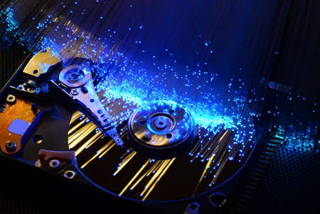 hard disk with colored fiber optics, tech background.