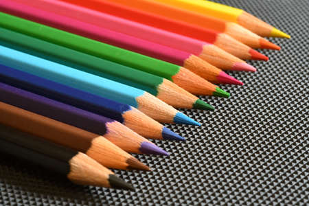 Color pencils on black rubber background. Close-up.