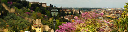 A view of the Fortress of Belvedere in Florence, taken from Piazzale Michelangelo on a spring day with purple flowered trees. Stock Photo