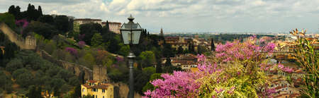 A view of the Fortress of Belvedere in Florence, taken from Piazzale Michelangelo on a spring day with purple flowered trees.