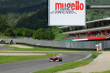 MUGELLO, ITALY 2012: Felipe Massa on Ferrari during the tests of the Formula 1 teams on the Mugello Circuit in Italy with the fans on the large central grandstand in the background and the Circuit logo. italy