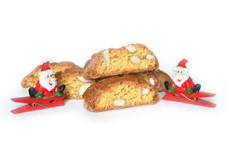 Close up on the cantucci or cantuccini with Santa toy on white background. Cantuccini are typical Tuscan dry biscuits, made with flour, eggs, yeast and almonds. Italy.