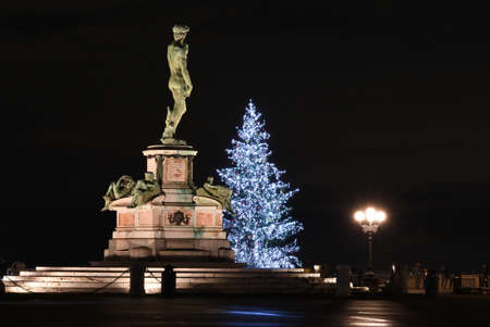 Bronze statue of David at Parco Michelangelo in Florence with illuminated Christmas tree in the background at evening. Florence, Italy.