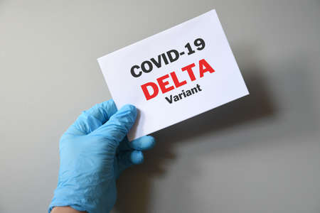 Doctor's hand in blue glove with white paper and text Covid-19 Delta Variant. Concept of medical variety delta variant and COVID-19. Concept words 'delta variant'. COVID-19 delta variant concept.