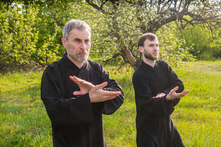 master and disciple of Taijiquan practice gymnastics in a savage blooming garden