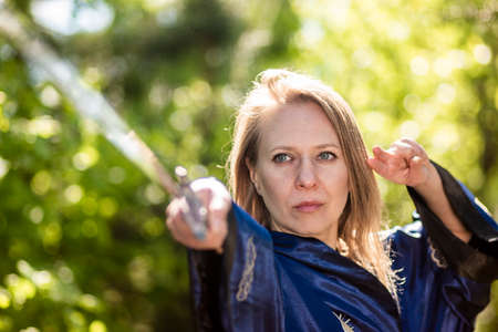 A woman warrior with a sword poses on a stump in the forest. Practice Wushu fencing in nature