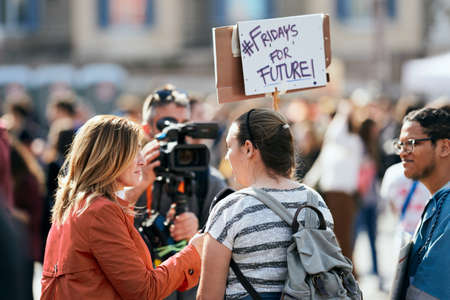 ROME, ITALY - April 19, 2019: People taking part in Fridays For Future Protest (School Strike For Climate, Greta Thunberg). A woman is being interviewed. Sign reading: