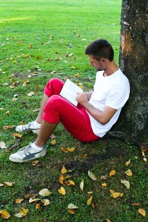 under the tree: Hombre leyendo bajo el �rbol Foto de archivo