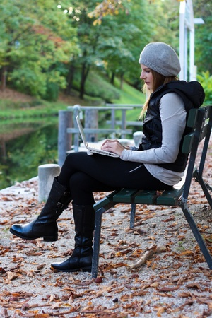 Woman sitting on a bench with her Laptop Stock Photo - 10888995