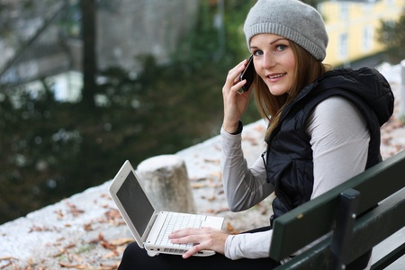 Woman on the Phone and Laptop next to a River Stock Photo - 10888992