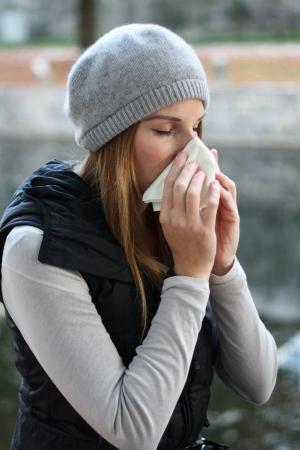 estornudo: mujer soplando en tejido Foto de archivo