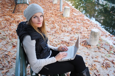 woman sitting on a bench with her laptop Stock Photo - 10888991