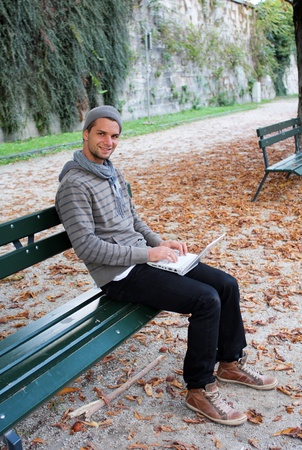 netbook: man writing on netbook on a bench outdoors Stock Photo
