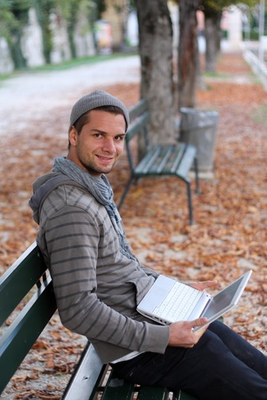 man sitting on a bench with netbook smiling photo