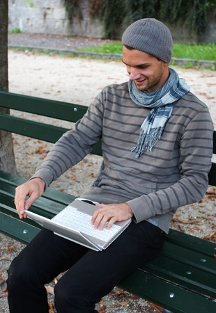 netbook: Man writing on Netbook on a Bench Outdoors
