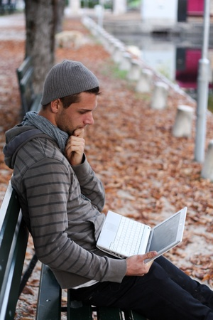 Man sitting on a Bench with netbook smiling Stock Photo