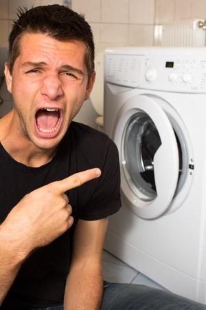 Young man unhappy with washing mashine photo