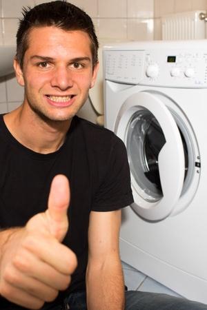 Young man happy with washing mashine photo