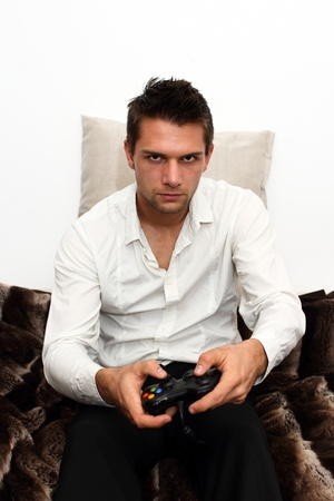 Gamer sitting on couch with controller and playing photo